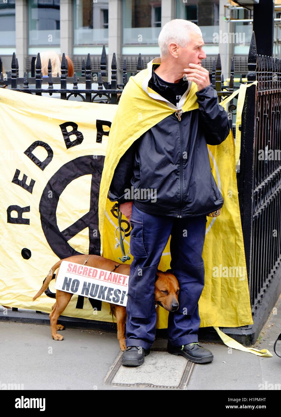 Un manifestant anti-austérité se trouve dans la rue à Londres comme son chien cowers entre ses jambes Photo Stock