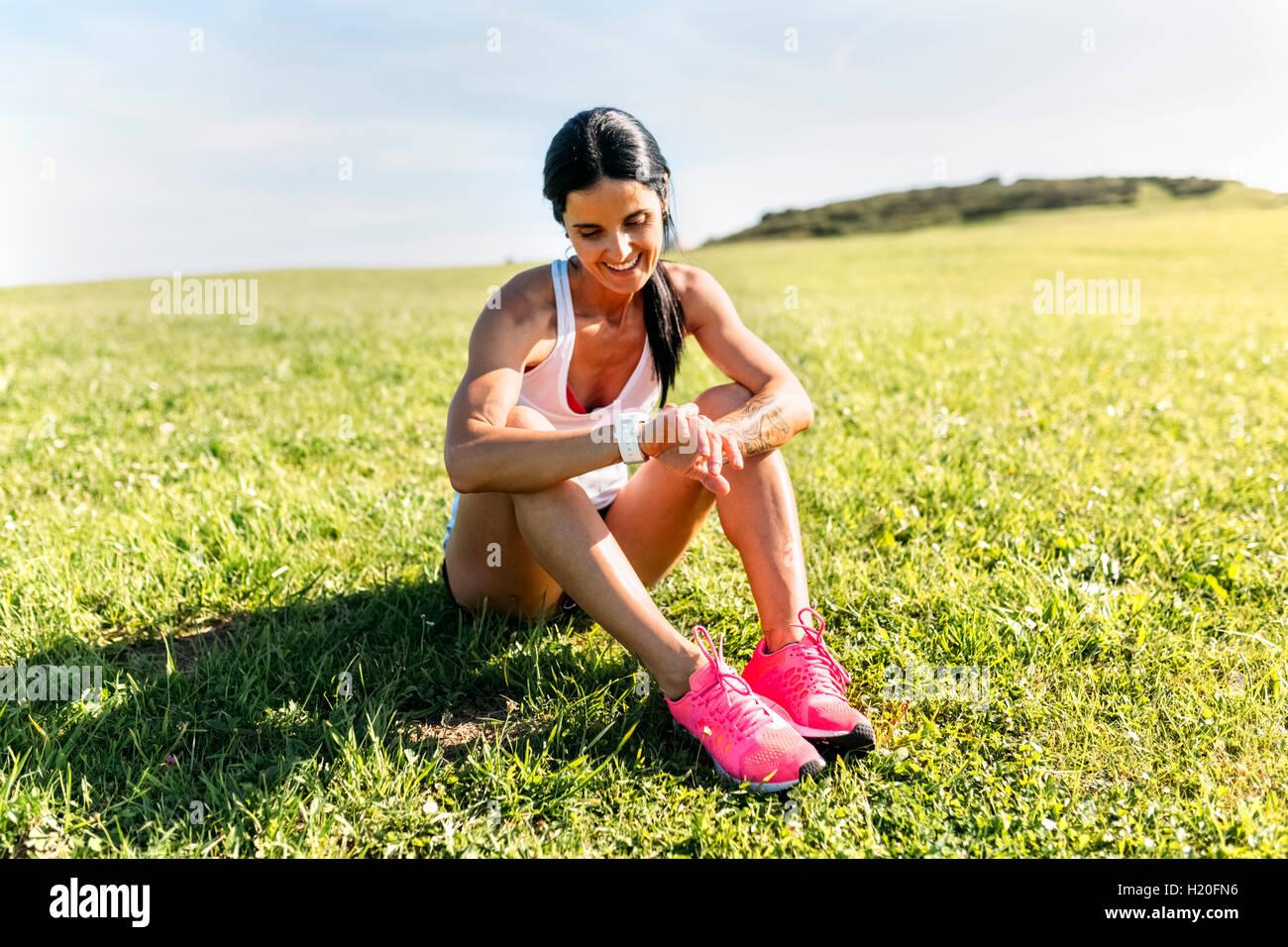 Woman sitting on grass, contrôle Moniteur de fréquence cardiaque Photo Stock