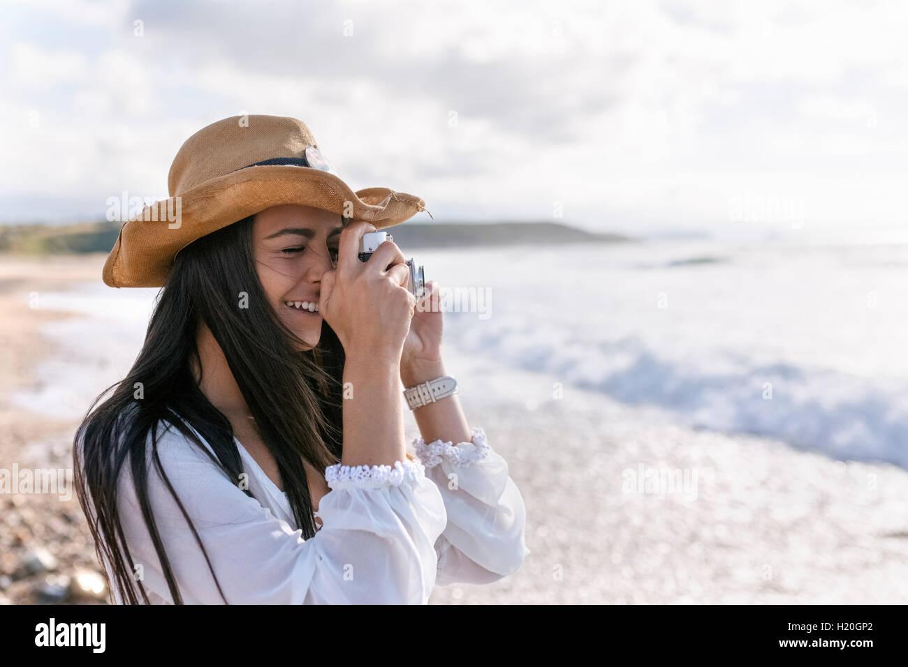 Les Asturies, Espagne, belle jeune femme avec un appareil photo sur la plage Banque D'Images
