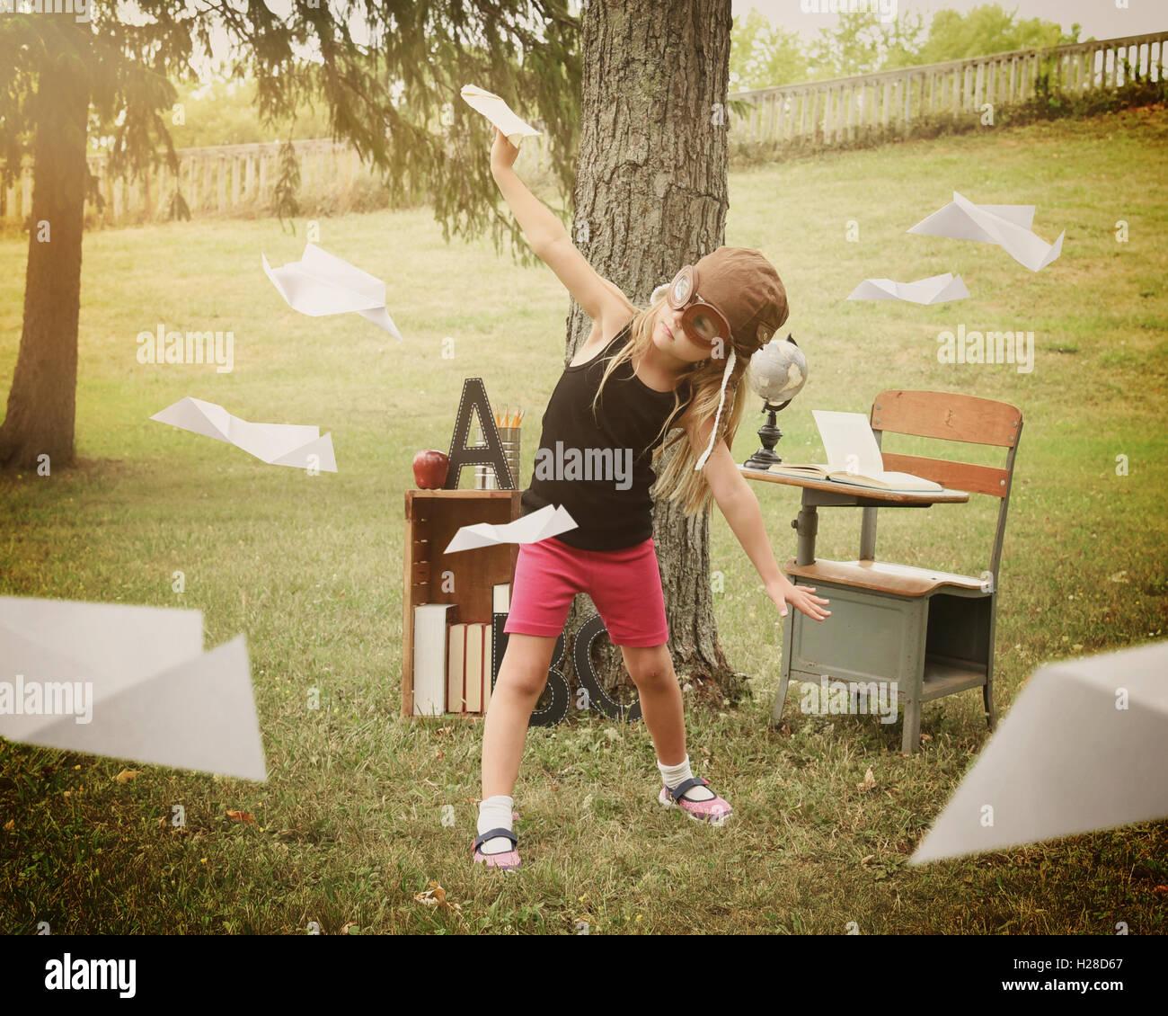 Un petit enfant fait semblant d'être un pilote aux commandes d'avions de papier dans une salle de classe à l'extérieur pour un concept d'éducation ou de la créativité. Banque D'Images