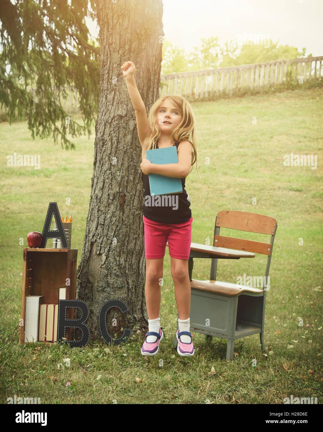 Un enfant saute vers le haut dans le bonheur à l'extérieur d'un bureau et d'adresses. L'utiliser pour un retour à l'école, l'éducation ou de succès concept Banque D'Images
