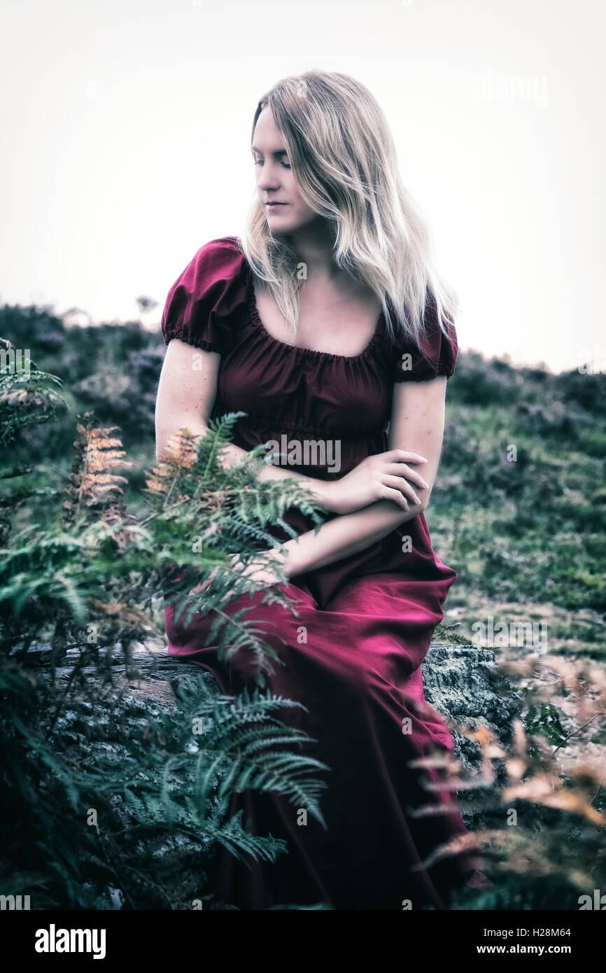 Une femme blonde dans une robe rouge est assis à l'extérieur dans la nature Banque D'Images