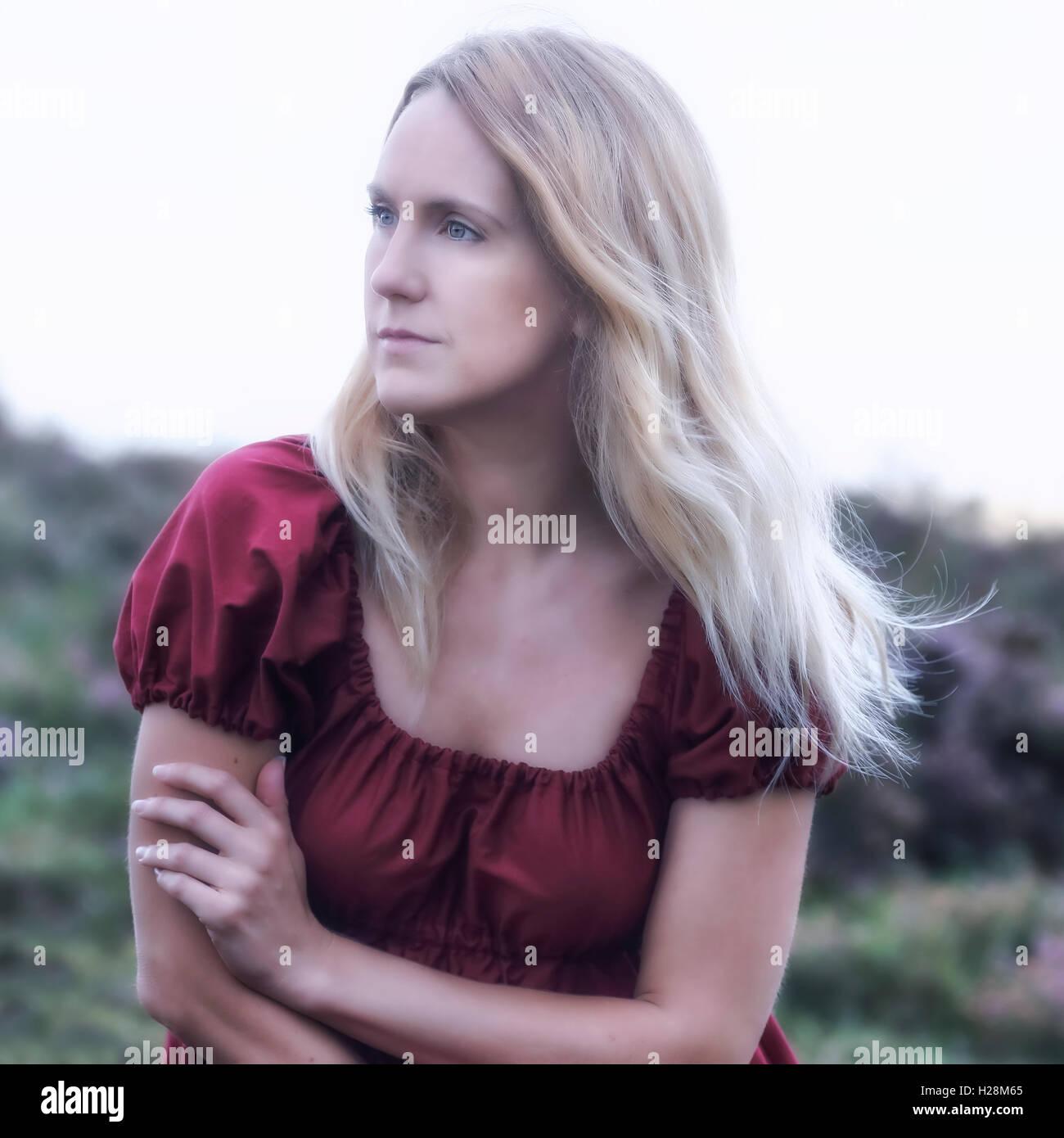 Portrait d'une femme blonde dans une robe rouge Banque D'Images