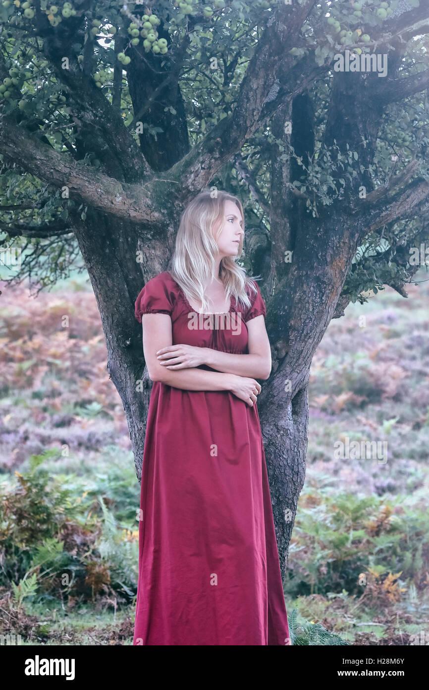 Une femme blonde avec une robe rouge est debout sous un arbre Banque D'Images