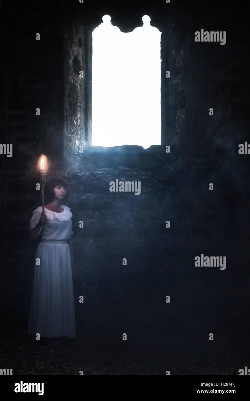 Une femme fantomatique dans une robe blanche est debout dans une vieille église avec une poussée Banque D'Images