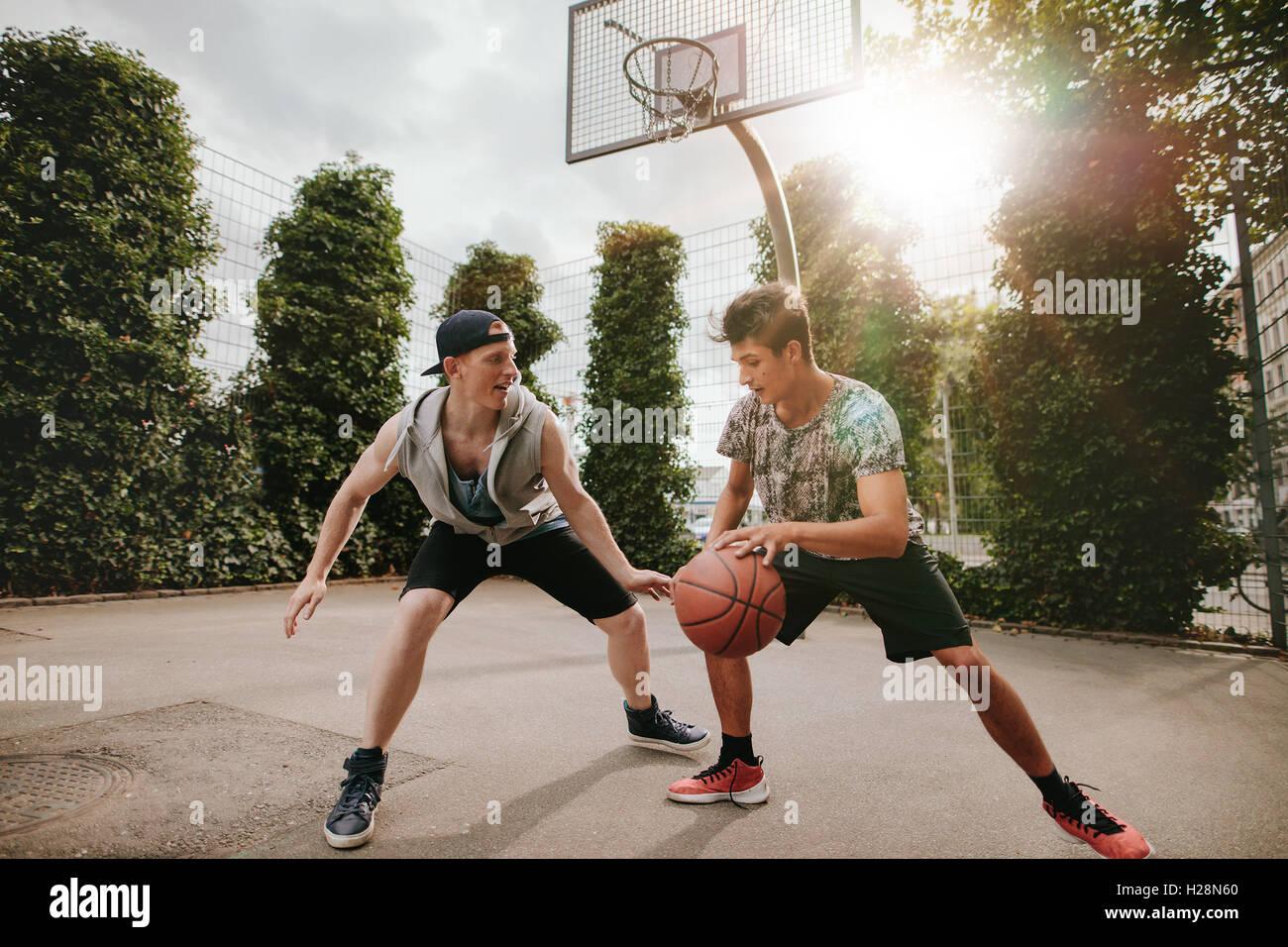 Amis adolescents jouer streetball les uns contre les autres et s'amuser. Deux jeunes hommes ayant un match de Photo Stock