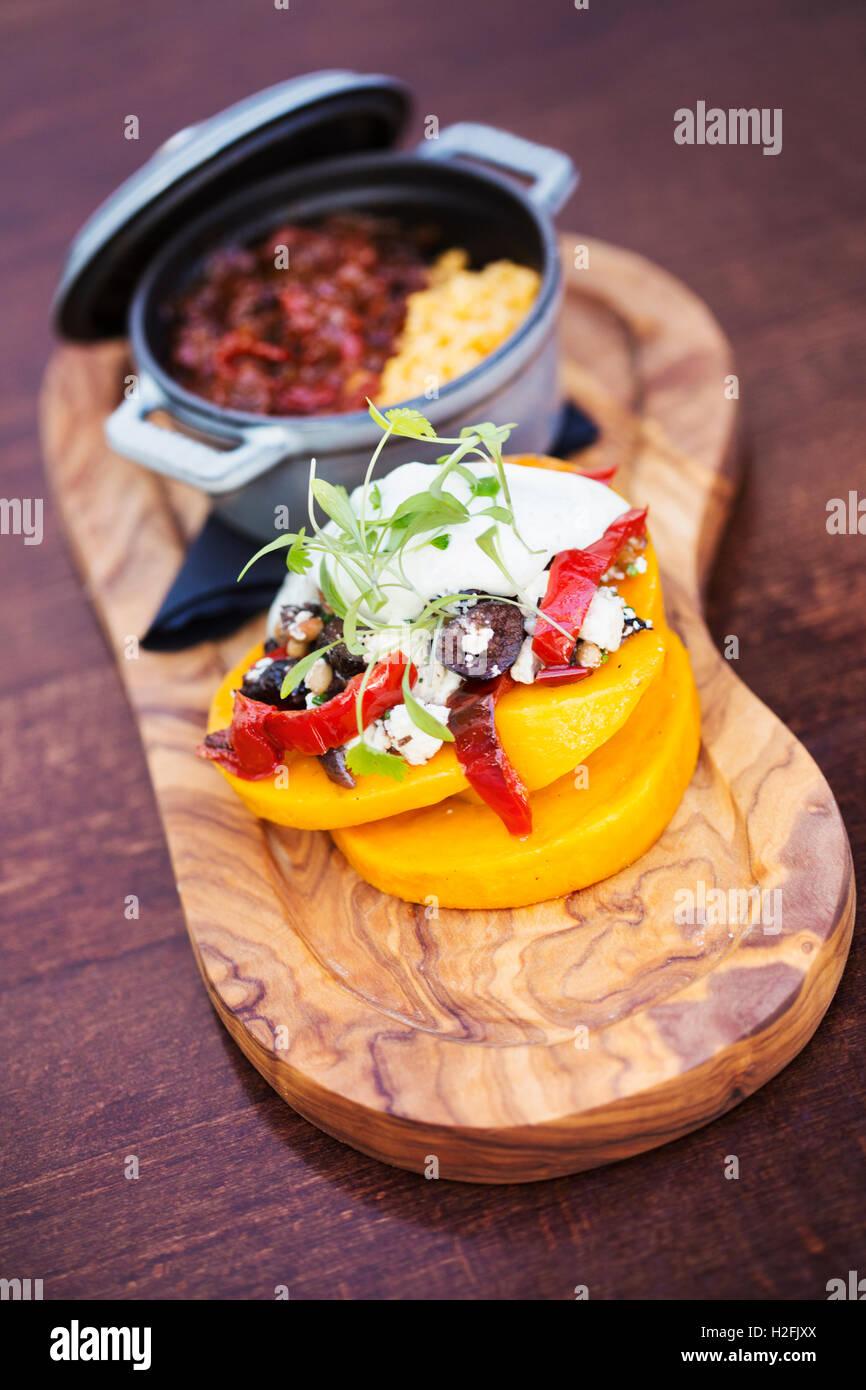 Le Red Lion house food village typiques. La trancheuse avec un petit pot de ragoût et une pile de légumes Photo Stock