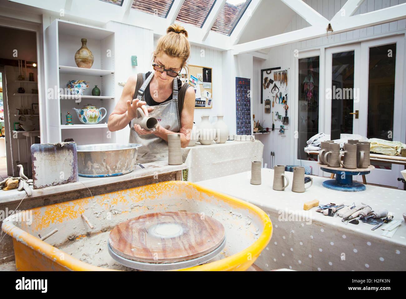 Un potter de la manipulation d'un pot d'argile humide, la préparer pour la cuisson au four. Banque D'Images