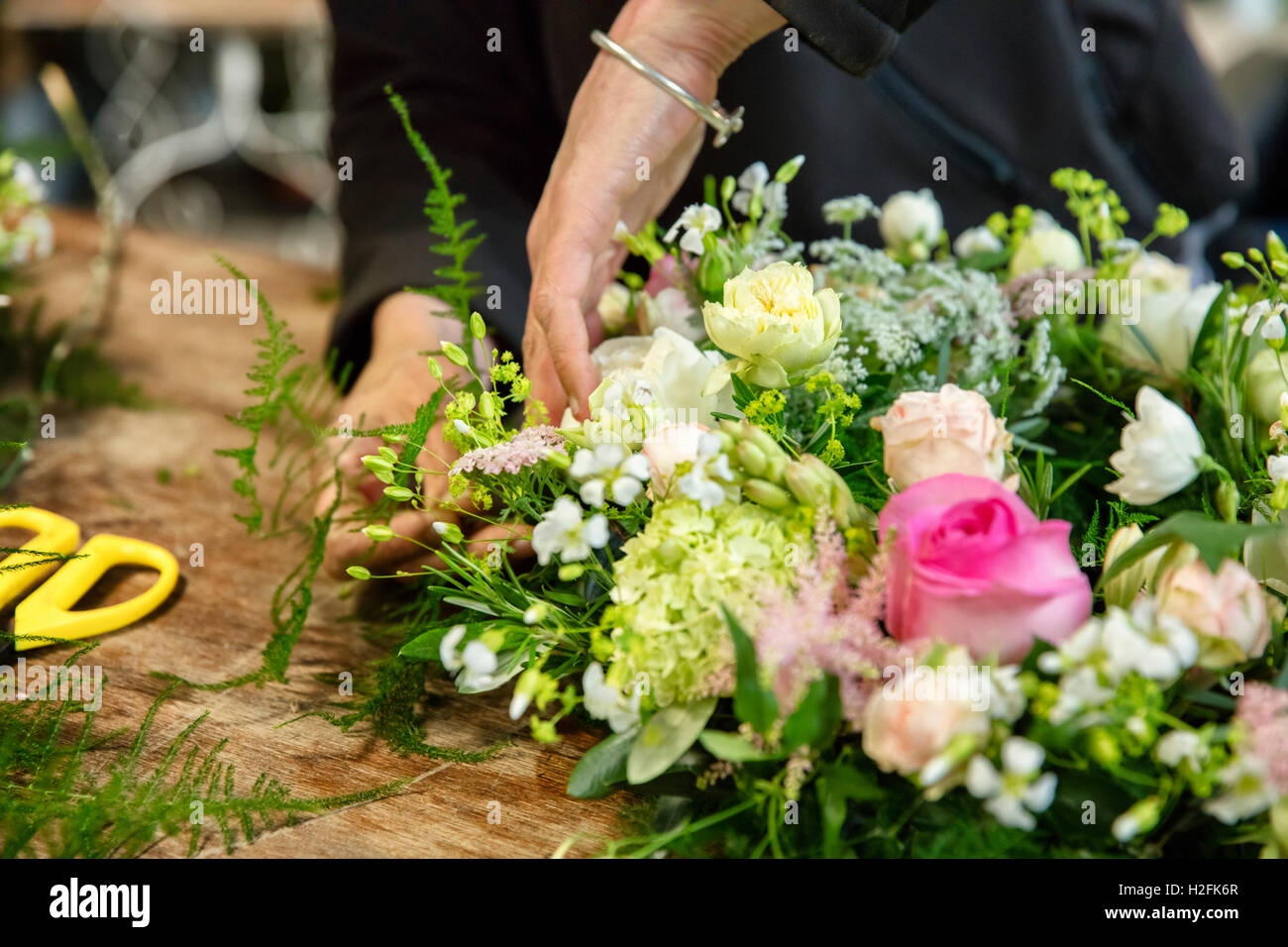Une femme travaillant sur un arrangement floral, un fleuriste. Photo Stock