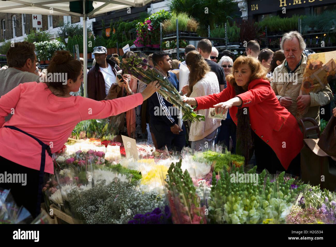 Columbia Road Flower Market, Londres, Angleterre, Royaume-Uni. Commerçant rue vente de fleurs, client payer Photo Stock
