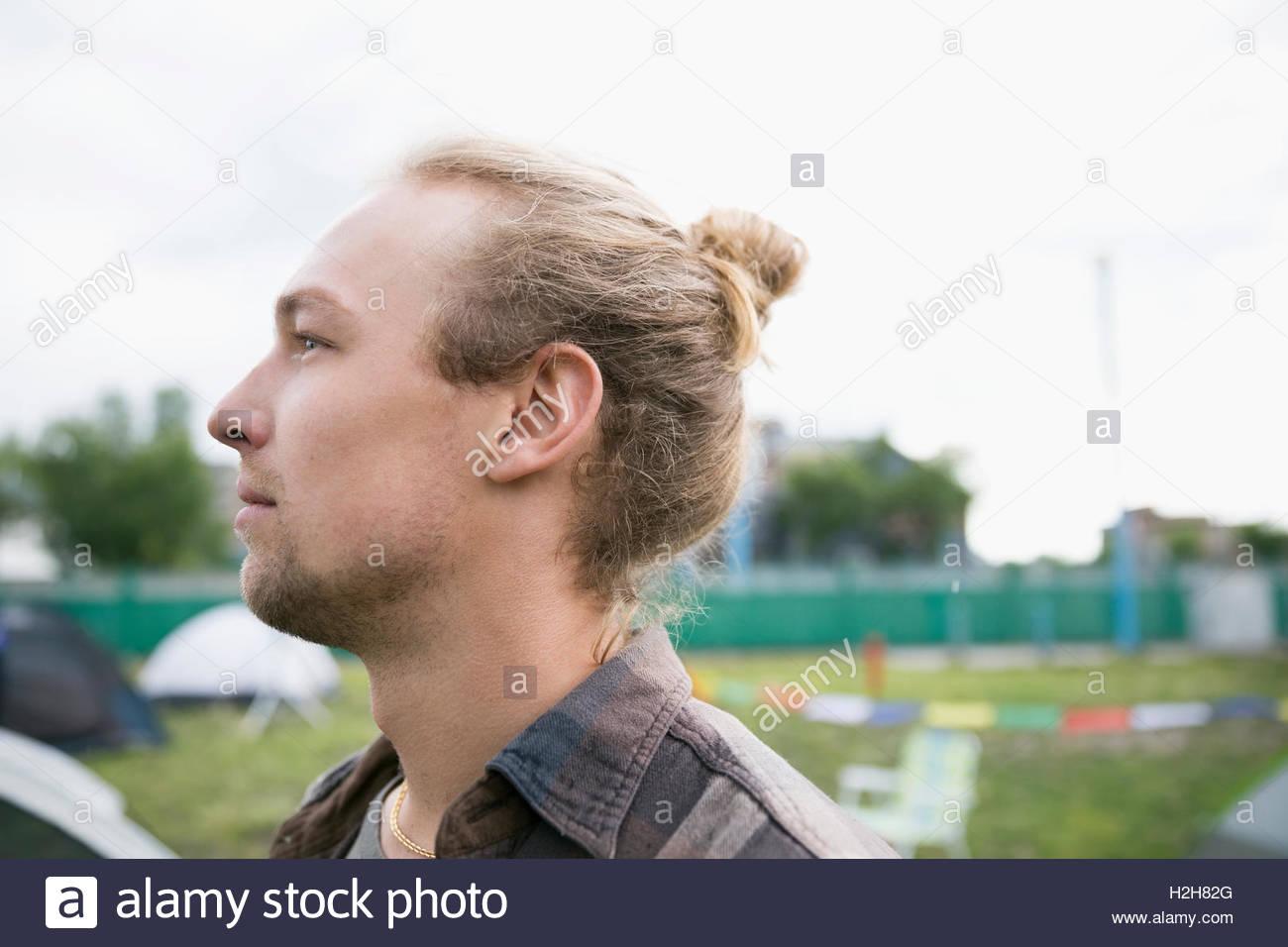 Portrait pensive young man blonde avec cheveux bun à loin à summer music festival camping Photo Stock
