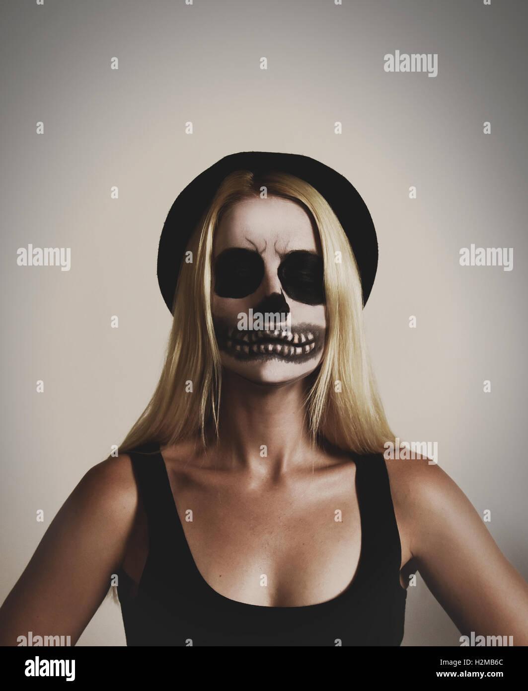Une jeune femme porte un masque effrayant skelton un miroir avec de la peinture noir et blanc sur un arrière-plan pour un isolé costum halloween Banque D'Images