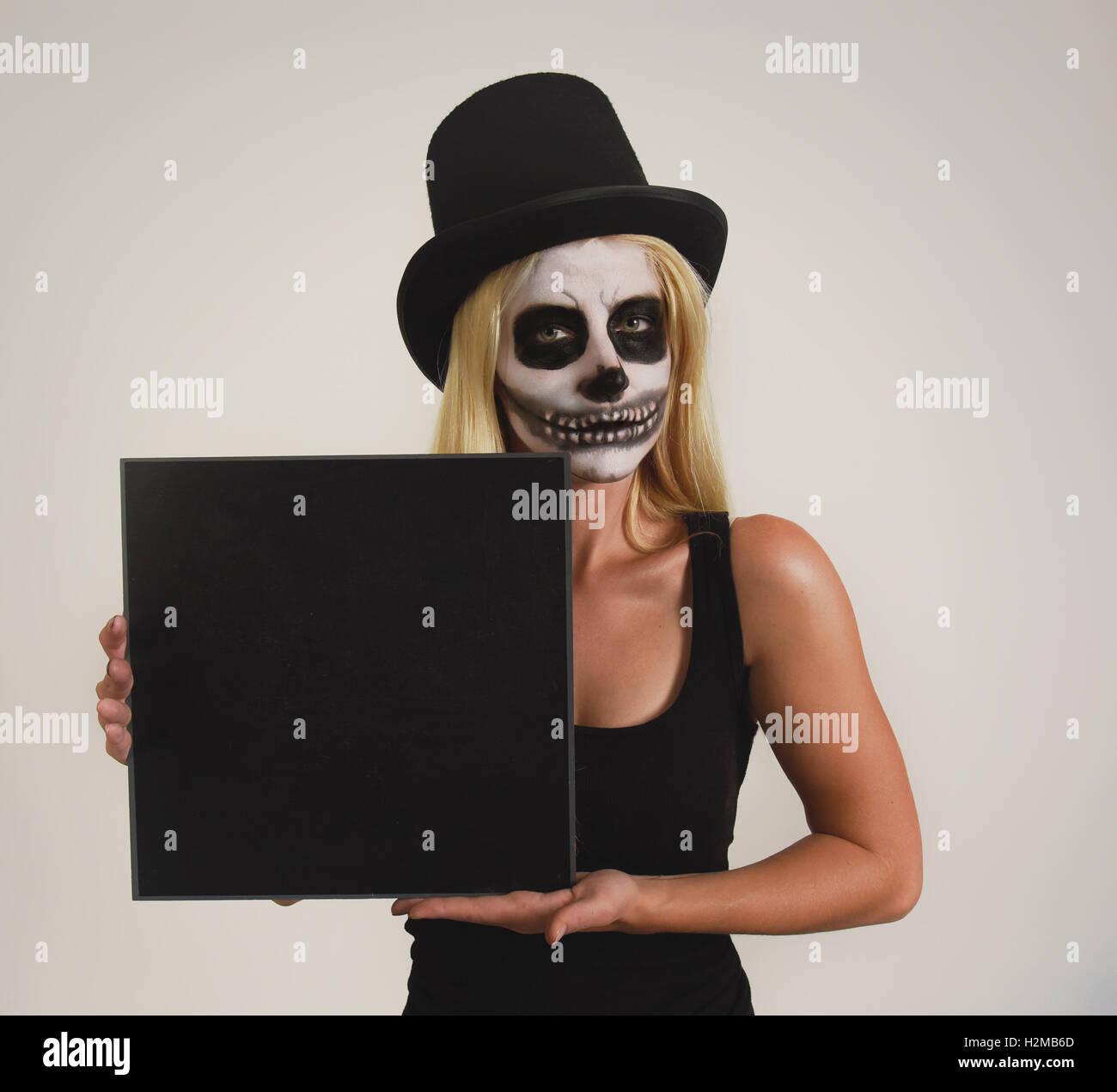 Une jeune fille porte un chapeau noir avec un squelette effrayant peinture maquillage sur son visage holding a blank sign pour un message d'halloween Banque D'Images