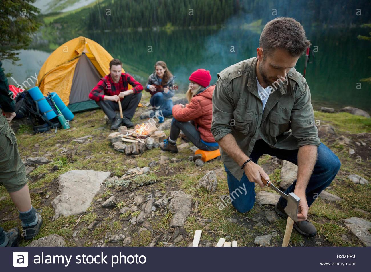 Homme fendre du bois avec hache de camp près de lakeside camping Photo Stock