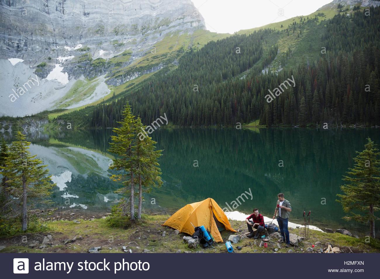 Amis du camping au camping au bord du lac de montagne à distance Photo Stock