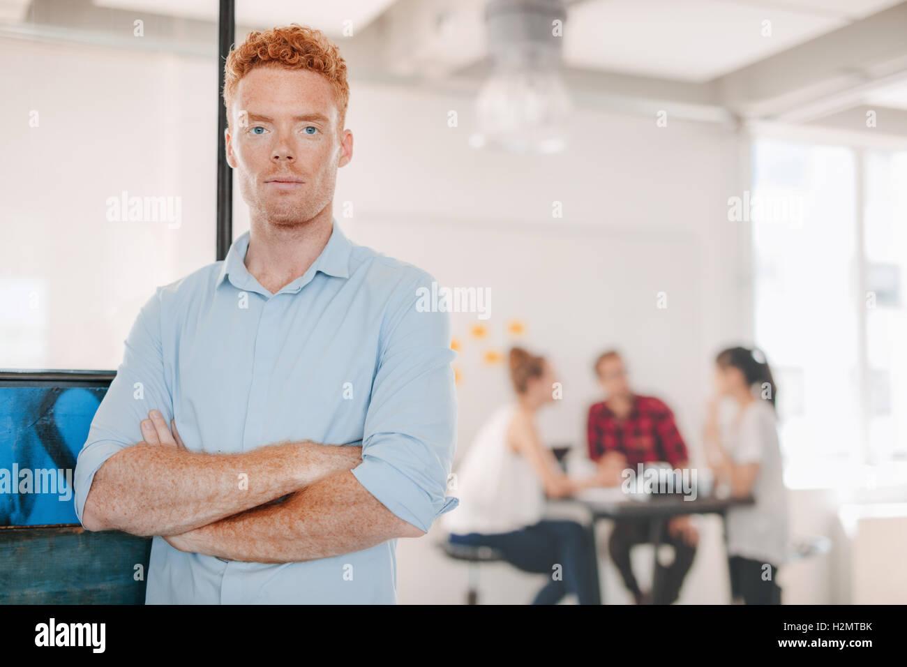Portrait of young businessman standing in office, les bras croisés et collègues réunion en arrière-plan. Banque D'Images