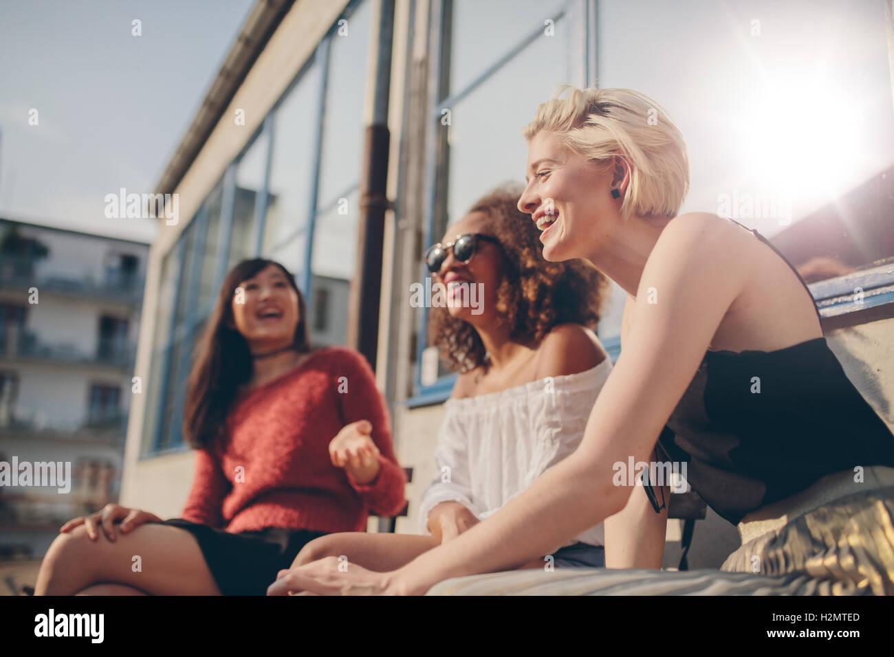 Groupe d'amies s'amuser tout en étant assis au café en plein air. Trois jeunes femmes assises Photo Stock