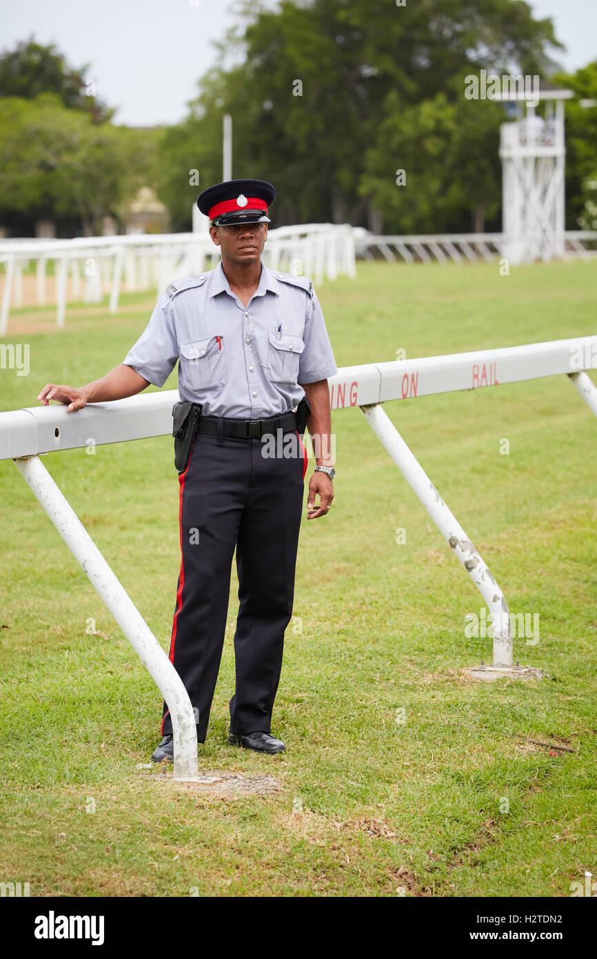 La Barbade Bridgetown hippodrome uniforme policier noir cours mâle homme manches courtes armes chapeau gendarme Photo Stock