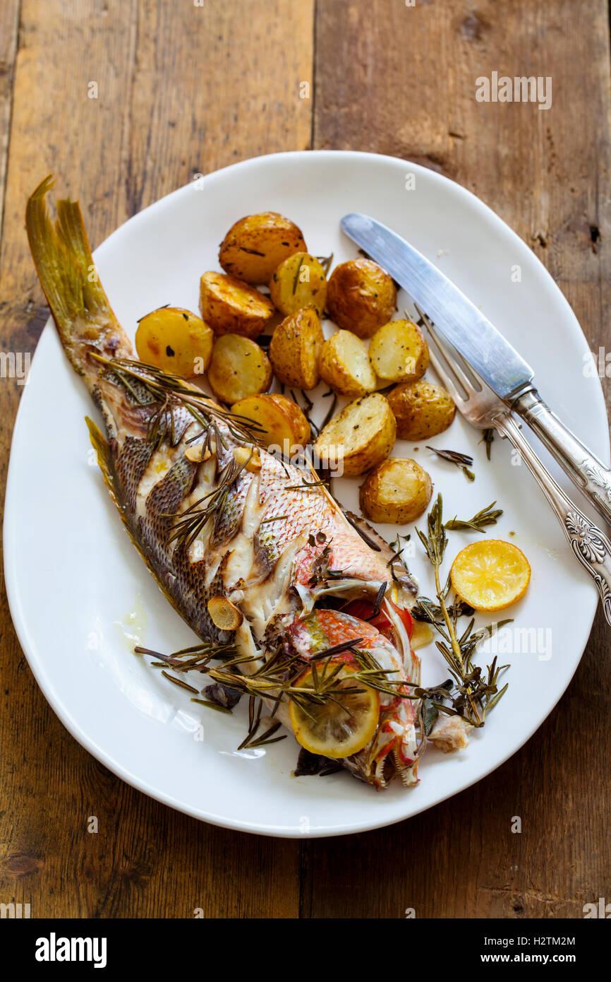 Le vivaneau rouge rôti avec pommes de terre au romarin rôti Photo Stock