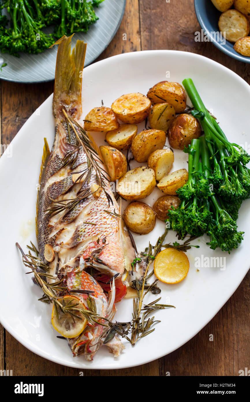 Le vivaneau rouge rôti au romarin rôti avec pommes de terre et brocolis Photo Stock