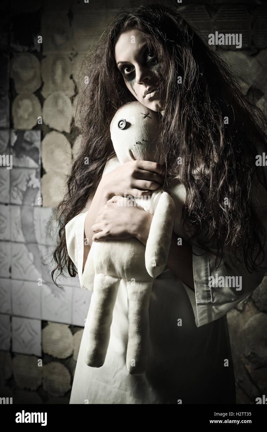 Style horreur shot: une étrange jeune fille triste avec moppet poupée dans les mains Photo Stock