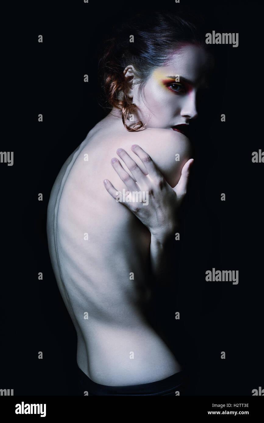Effrayant sombre portrait d'une jeune fille parmi l'obscurité Photo Stock