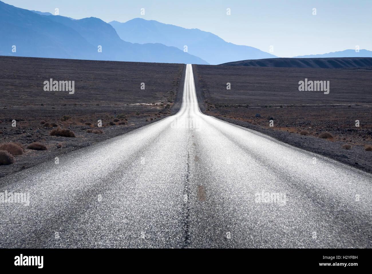 Route droite en direction de montagnes en horizon à Death Valley, Etats-Unis Photo Stock