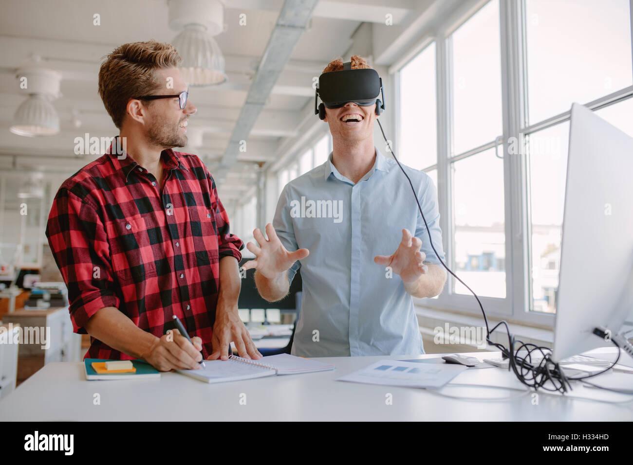 Photo de deux jeunes hommes lunettes de réalité virtuelle à l'essai dans le bureau. Businessman wearing lunettes Banque D'Images