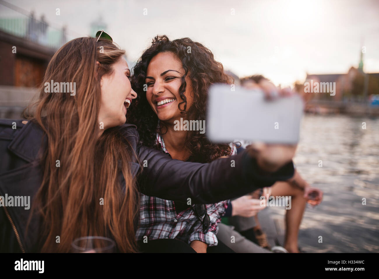 Cheerful young women friends en tenant par les selfies lake. Meilleurs amis de s'amuser ensemble. Banque D'Images