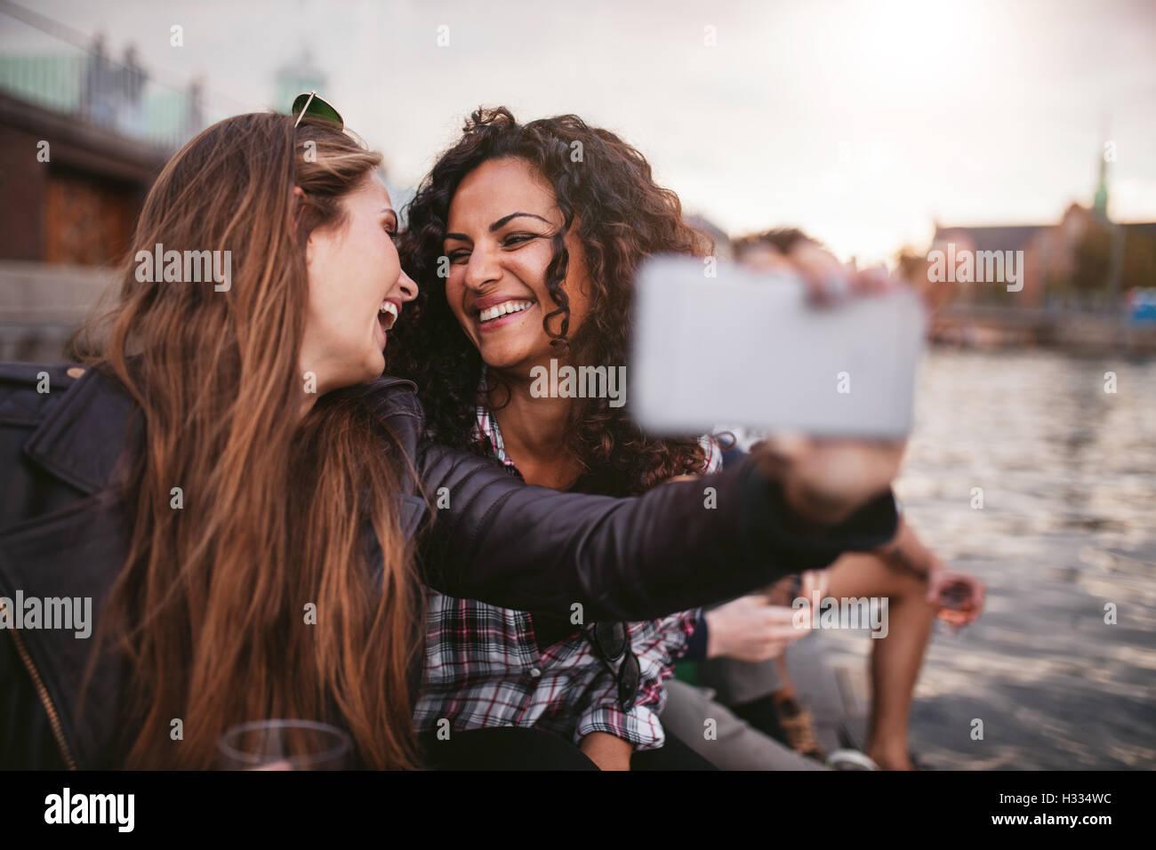 Cheerful young women friends en tenant par les selfies lake. Meilleurs amis de s'amuser ensemble. Photo Stock