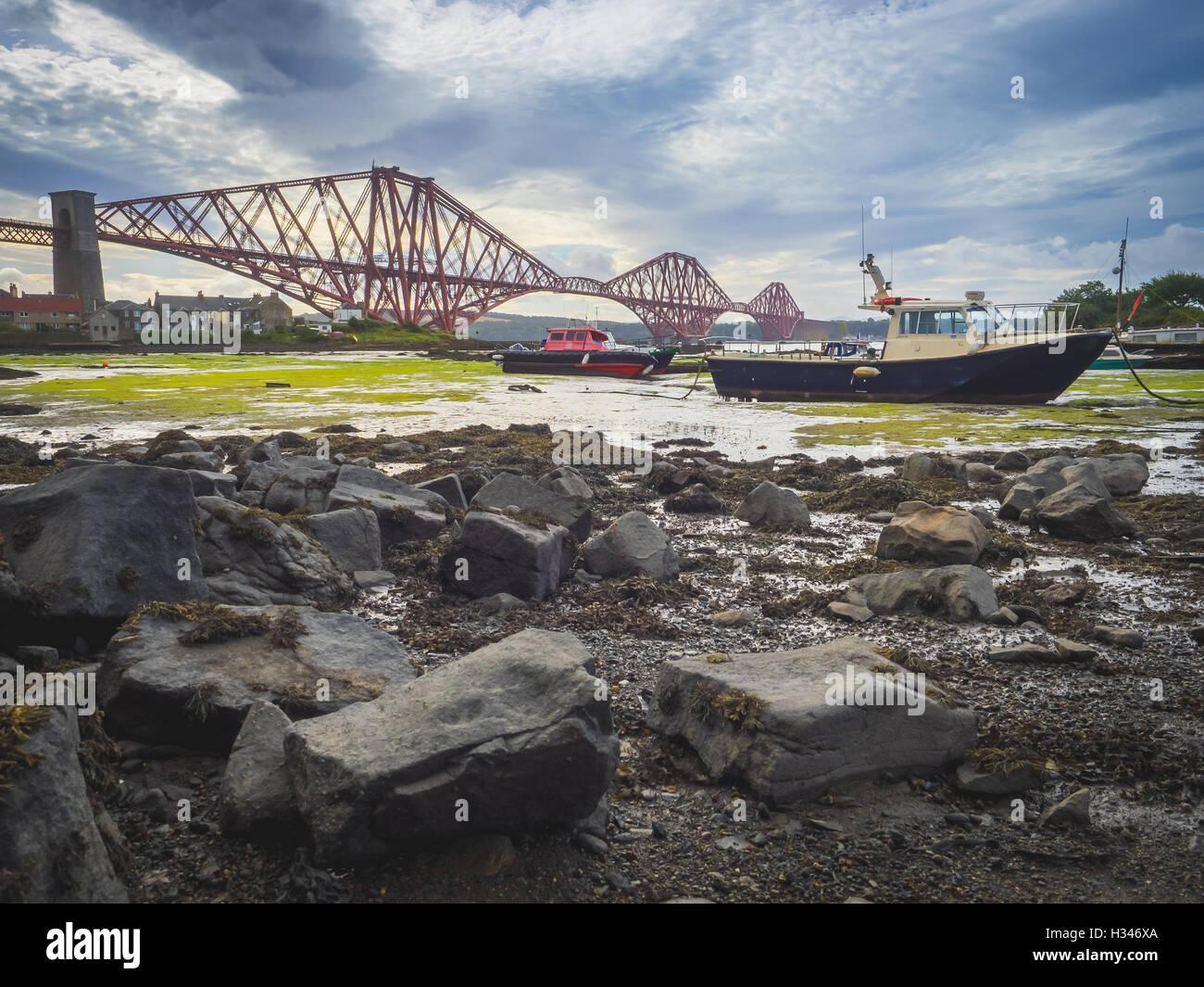 Bateau amarré en face de la Forth Rail Bridge à Édimbourg, Écosse, reliant les villes du nord Photo Stock