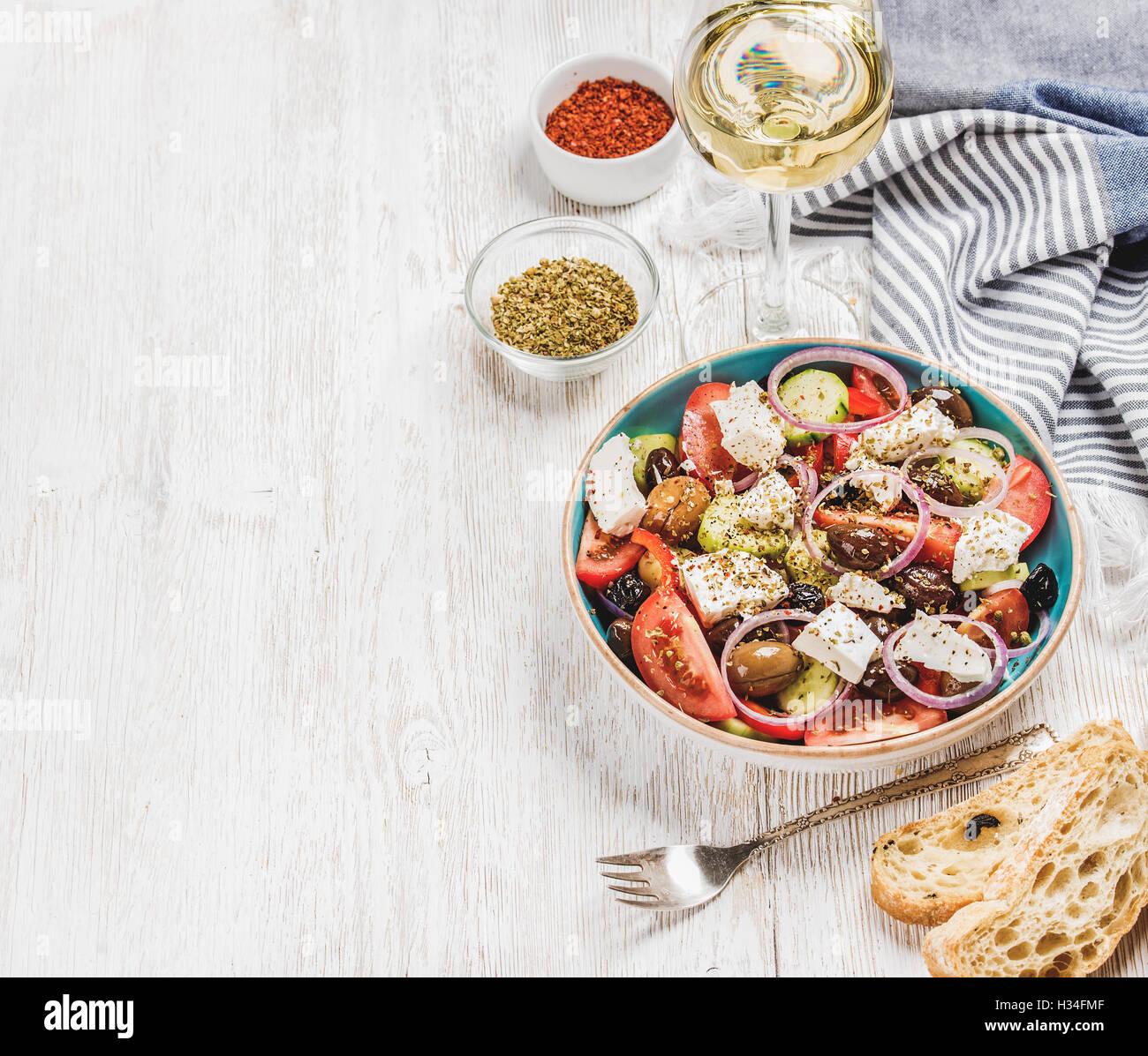 Salade grecque avec du pain, des herbes et le verre de vin blanc Photo Stock