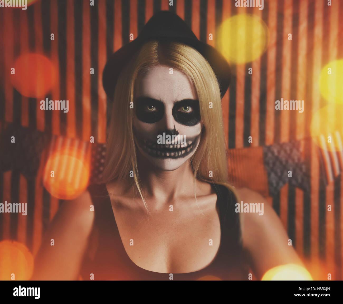 Une femme porte skeleton maquillage sur son visage avec des feux d'un parti d'orange halloween costume ou idée. Banque D'Images