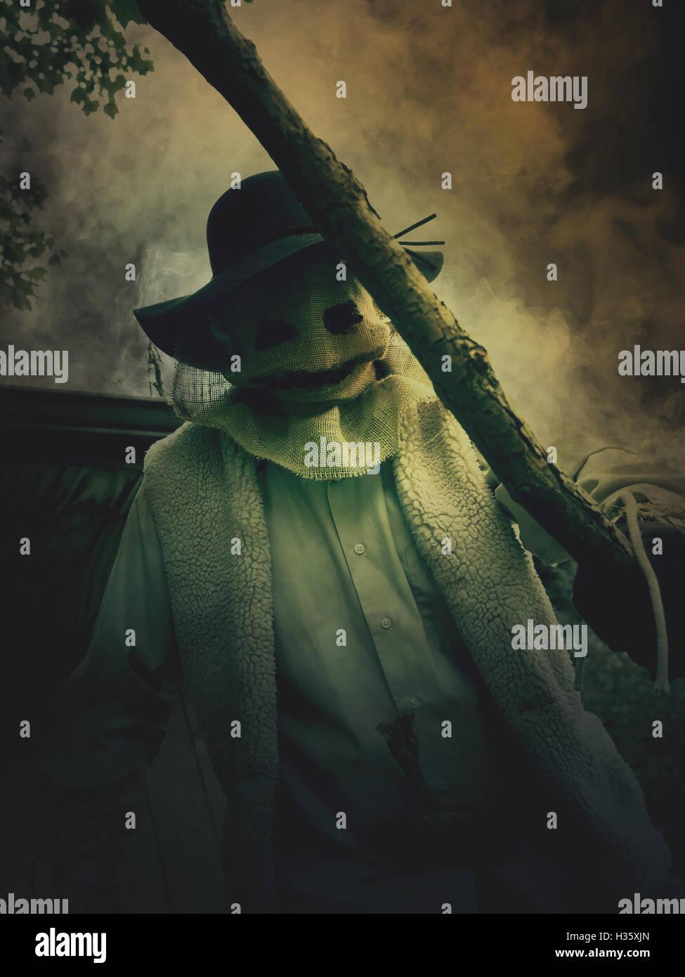 Un peu d'evil scarecrow l'homme est titulaire d'un bâton avec un masque de monstre de jute sur son visage pour un cauchemar halloween concept. Banque D'Images