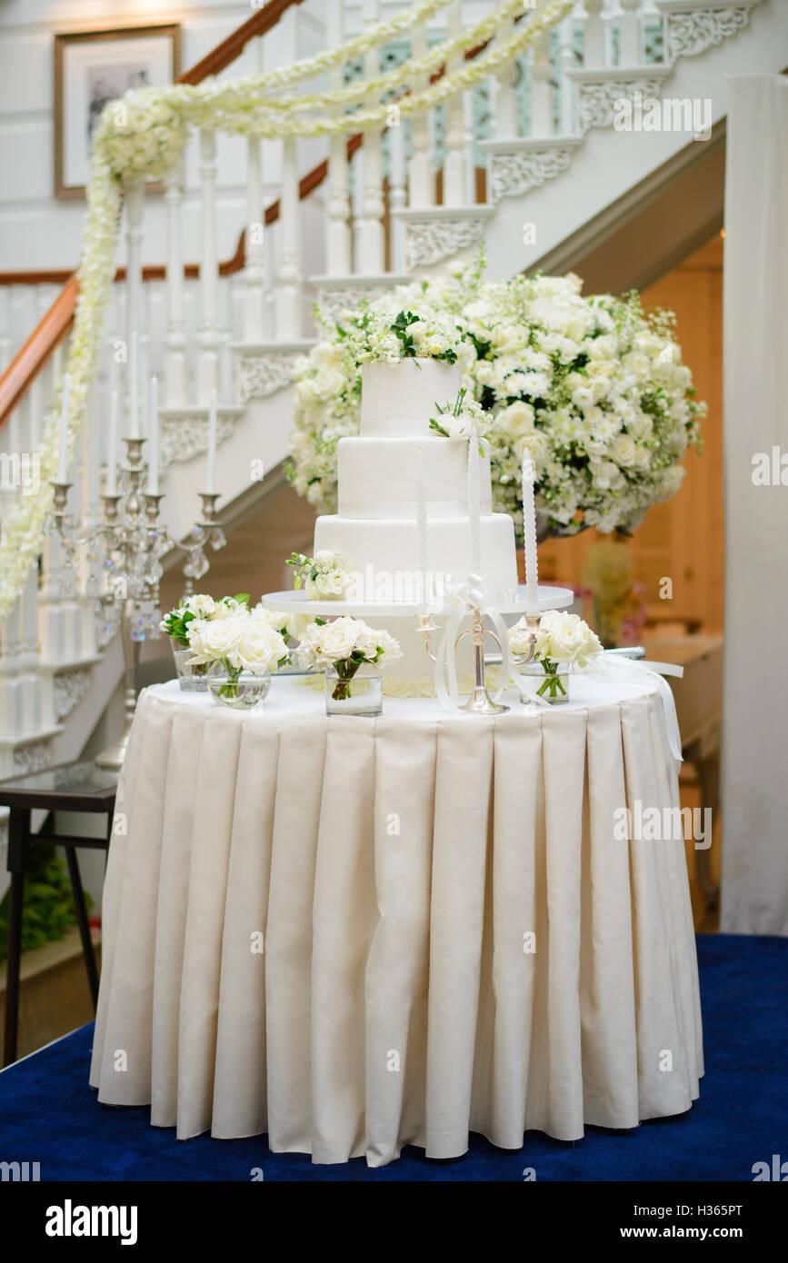 Gâteau de mariage entouré de fleurs blanches Photo Stock