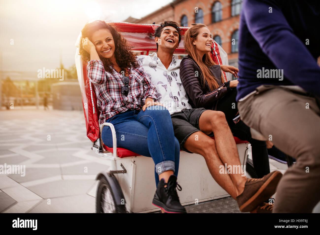 Teenage friends enjoying tricycle ride dans la ville. Les adolescents équitation sur tricycle sur route et Photo Stock