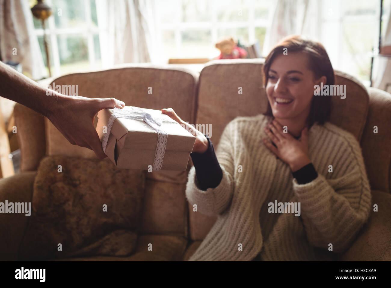 Surprenant homme femme avec un cadeau dans la salle de séjour Photo Stock