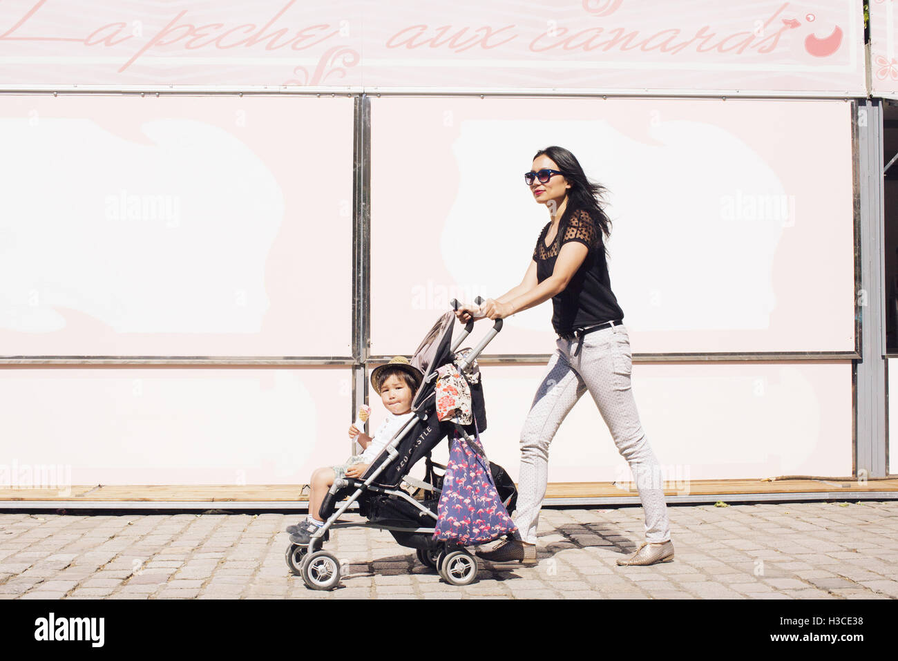 Mère poussant petit garçon en poussette on sidewalk Photo Stock