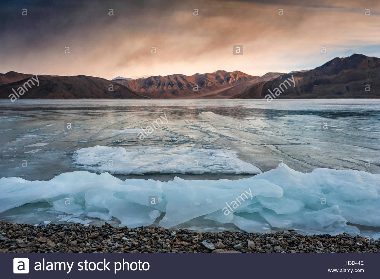 Vue panoramique sur lac gelé contre le ciel au coucher du soleil Photo Stock