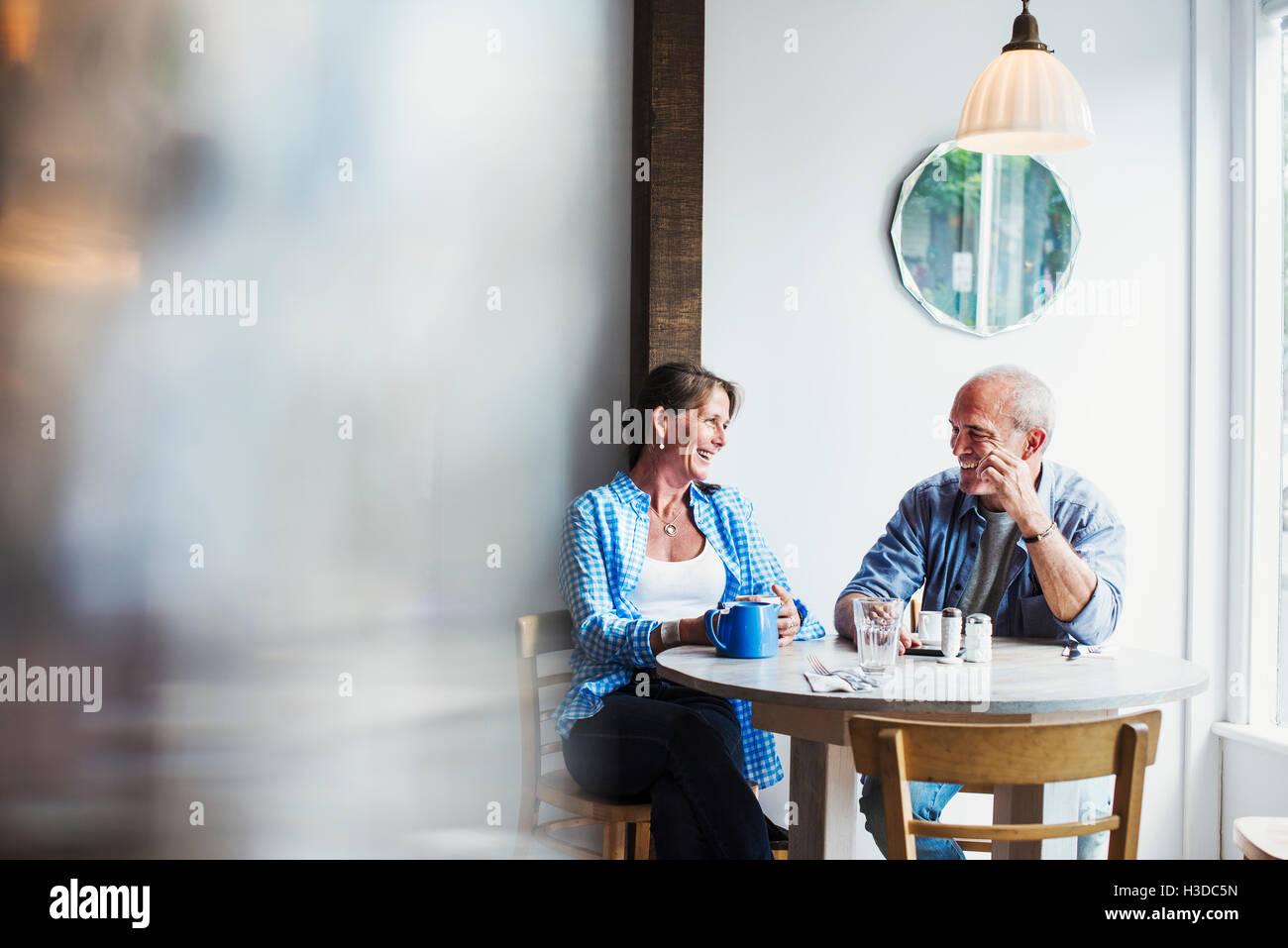 Deux personnes assises à une table de café. Avant-plan flou. Photo Stock