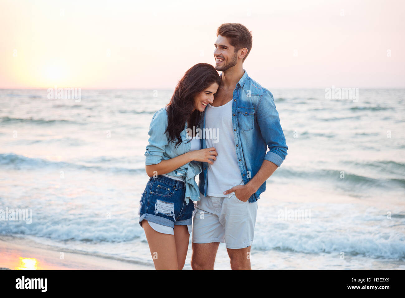 Happy young couple hugging and laughing sur la plage Photo Stock