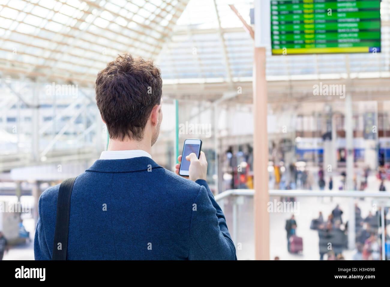 L'envoi de message texte voyageur sur smartphone avec l'horaire des trains en arrière-plan Photo Stock