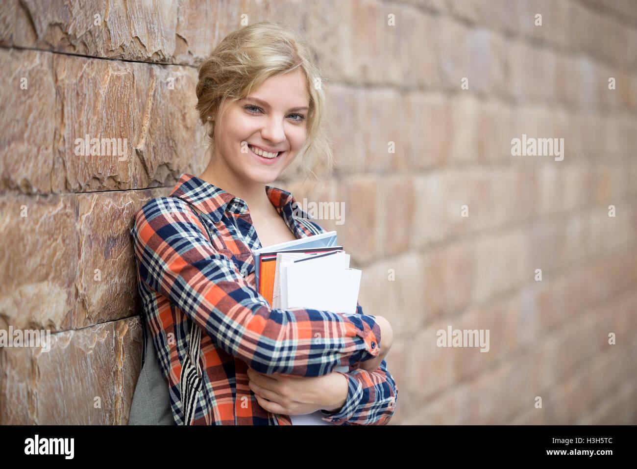 Portrait d'un étudiant avec un books contre le mur de brique Photo Stock