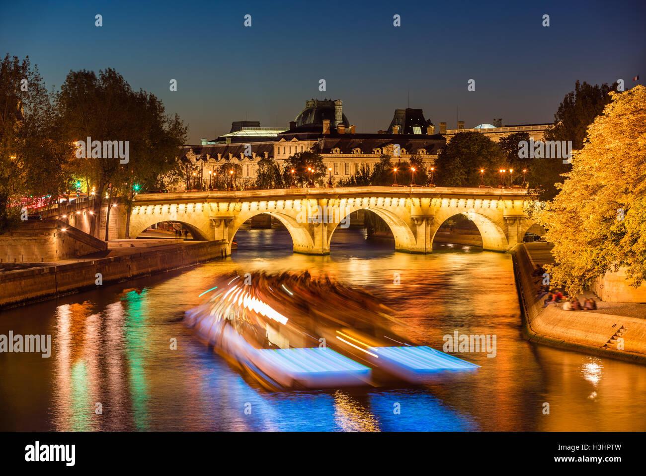 Pont Neuf et lumineux Seine au crépuscule avec les lumières et l'embarcation. L'Ile de la Cité, Photo Stock