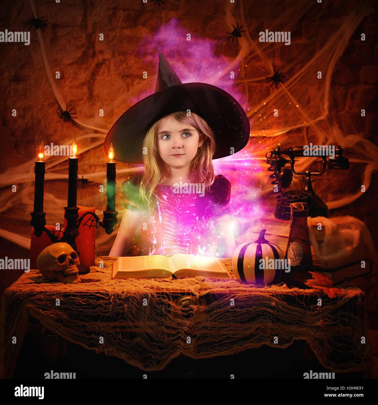 Une petite fille est habillé dans un costume wicth halloween avec un livre de sorts de magie pour une imagination ou scary story id Banque D'Images