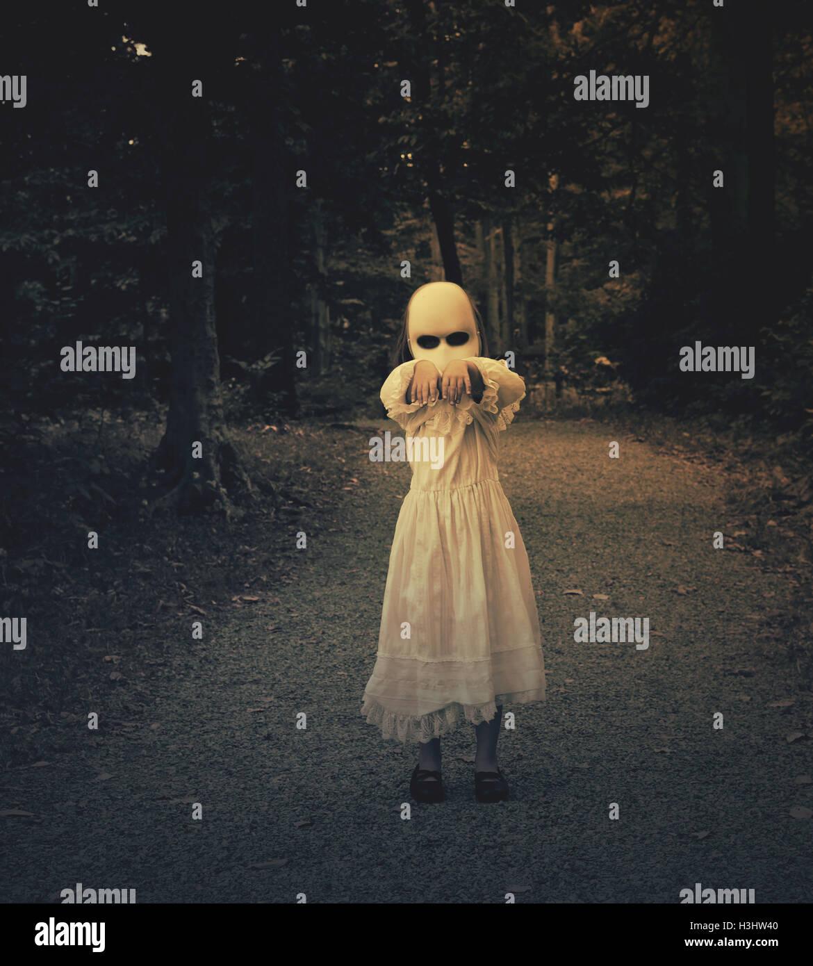 Une peur mal ghost girl vêtue d'une robe blanche et le visage marche dans les bois sombres et ses mains. Photo Stock
