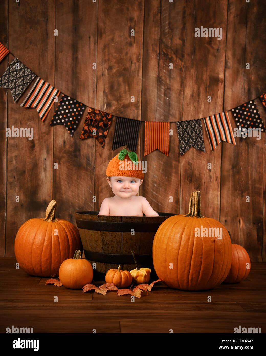 Un peu mignon bébé est assis dans un panier de bois avec automne halloween pumpkins autour de l'enfant pour un message portrait de saison Banque D'Images