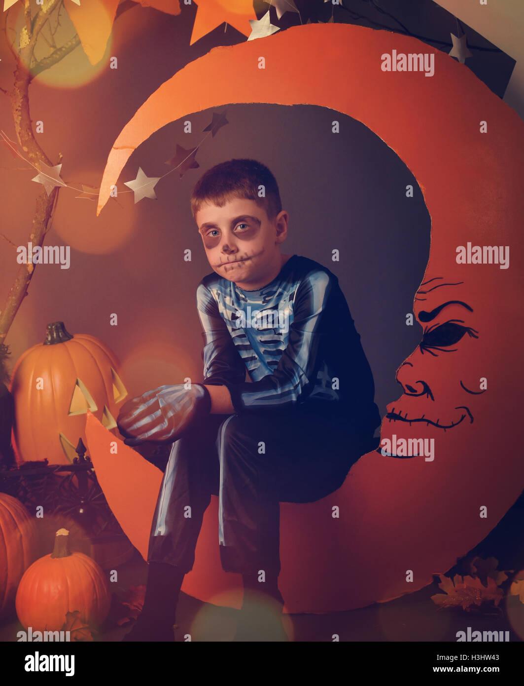 Un garçon est vêtu d'un costume de squelette Halloween et assis sur une lune orange avec un visage et des étoiles pour un portrait de nuit. Banque D'Images