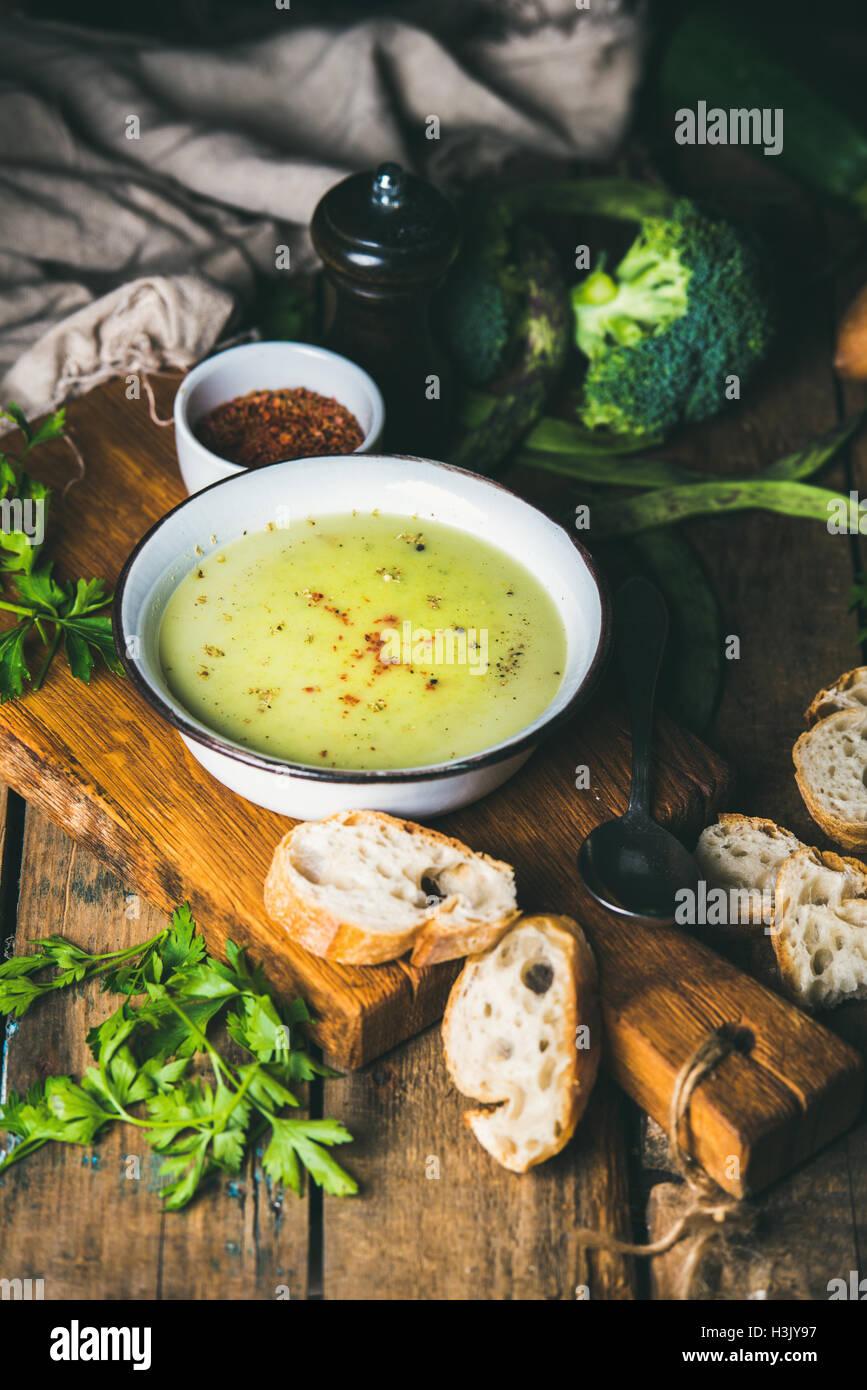 Des pois, du brocoli, des courgettes soupe de crème avec des tranches de pain baguette Photo Stock