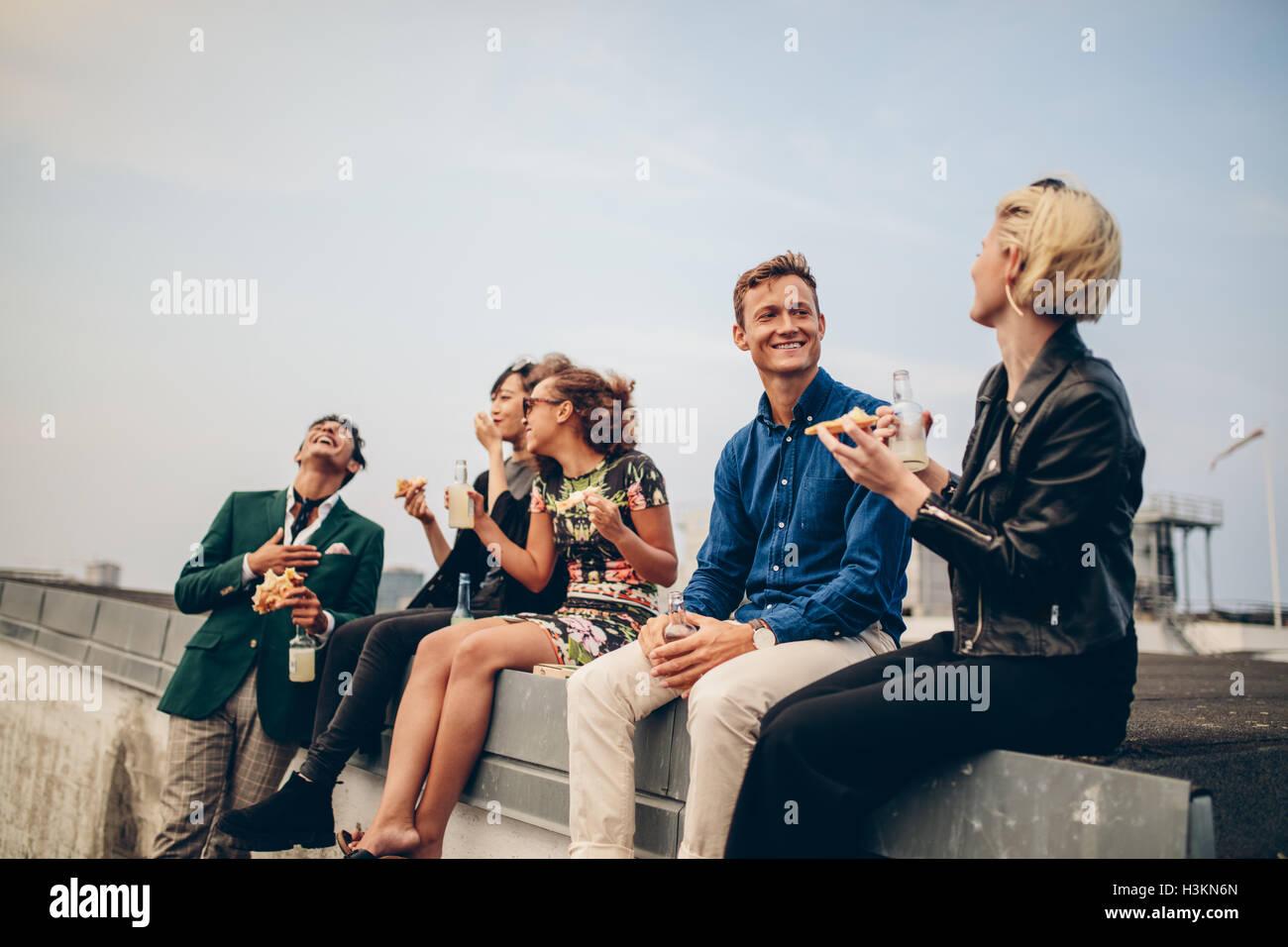 Groupe d'amis à faire la fête sur la terrasse, boire et manger. Les jeunes, hommes et femmes, de prendre Photo Stock